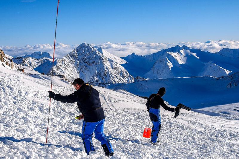dos personas realizando un curso de arva buscando entre la nieve