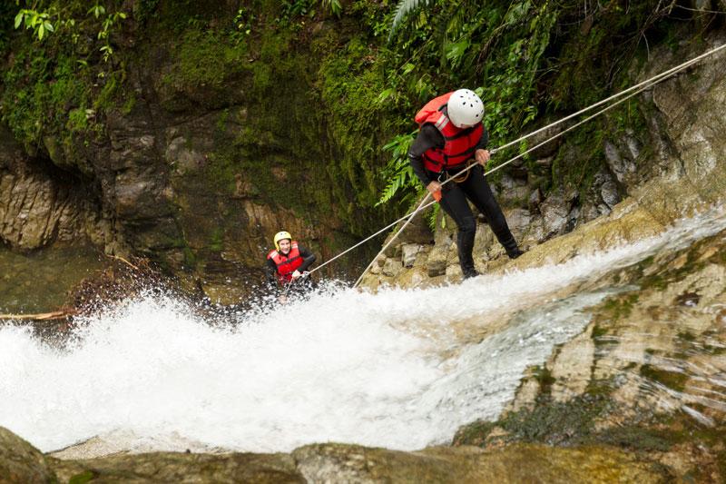 cascada de agua con dos personas realizando rappel en un curso de barrancos