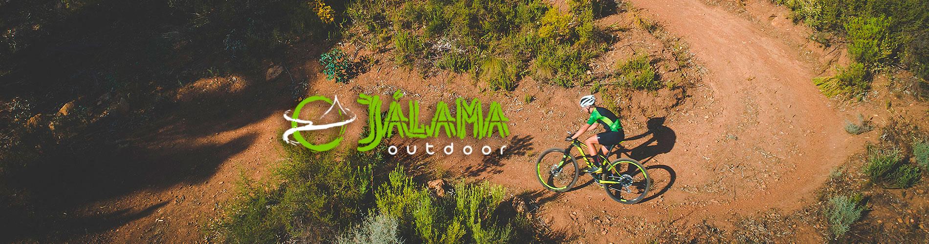 curva de un camino de tierra con piedras y una persona bajando por ella en biciceta