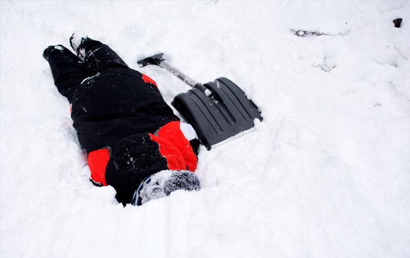 pala en una nieve y una persona tumbada para realizar un simulacro de montaña