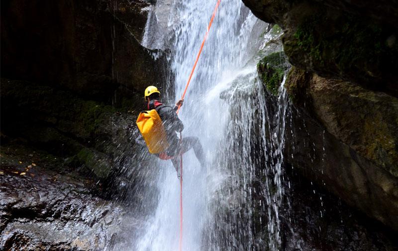 persona realizando un rappel en una cascada de agua con una cuerda roja en una ruta de barrancos