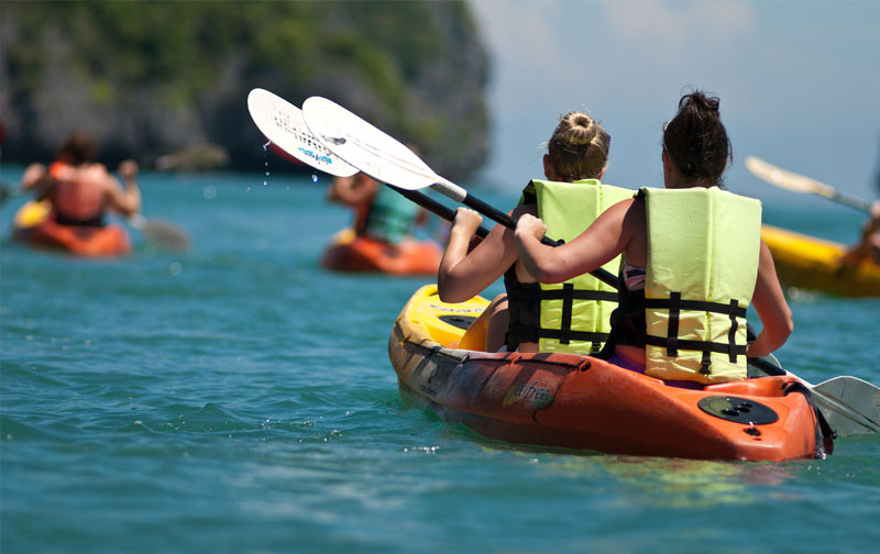 dos chicas montadas en un kayack con remos en medio de un pantano embalse realizando un ruta con mas personas